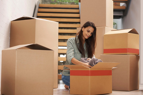 girl-packing-her-clothes-in-a-box-before-moving-to-a-new-house
